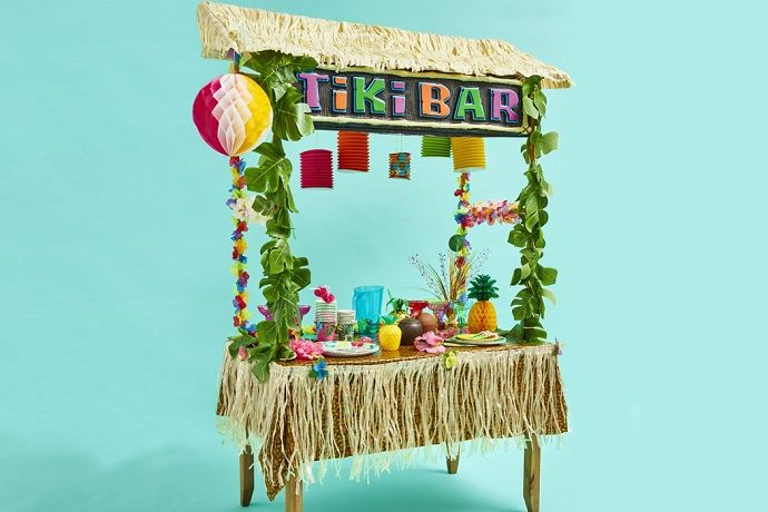 Tiki Bar decorated with sign, leaf garlands, hibiscus flower garlands and Hawaiian-themed tableware.