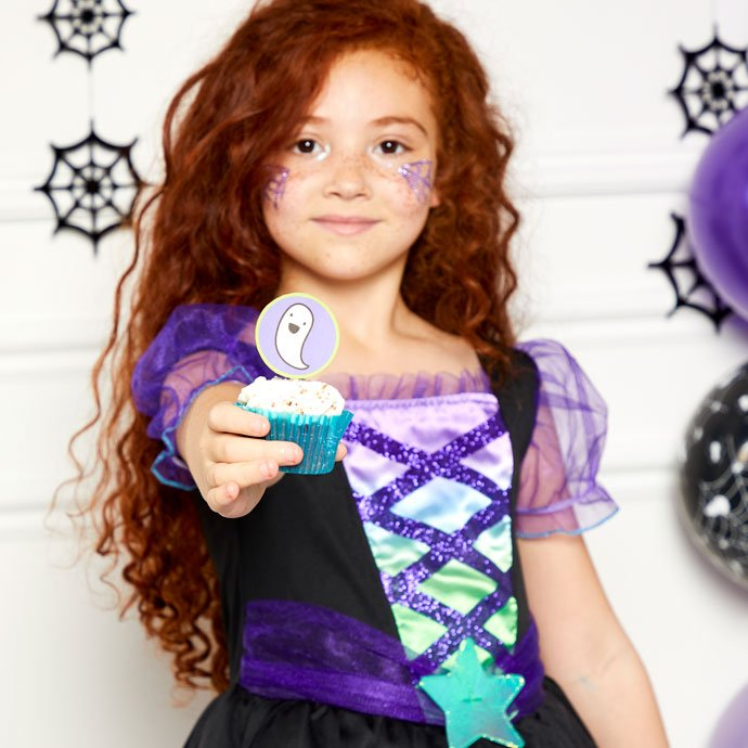 A little girl in a witch costume is holding a cupcake with a topper and offering it to the reader