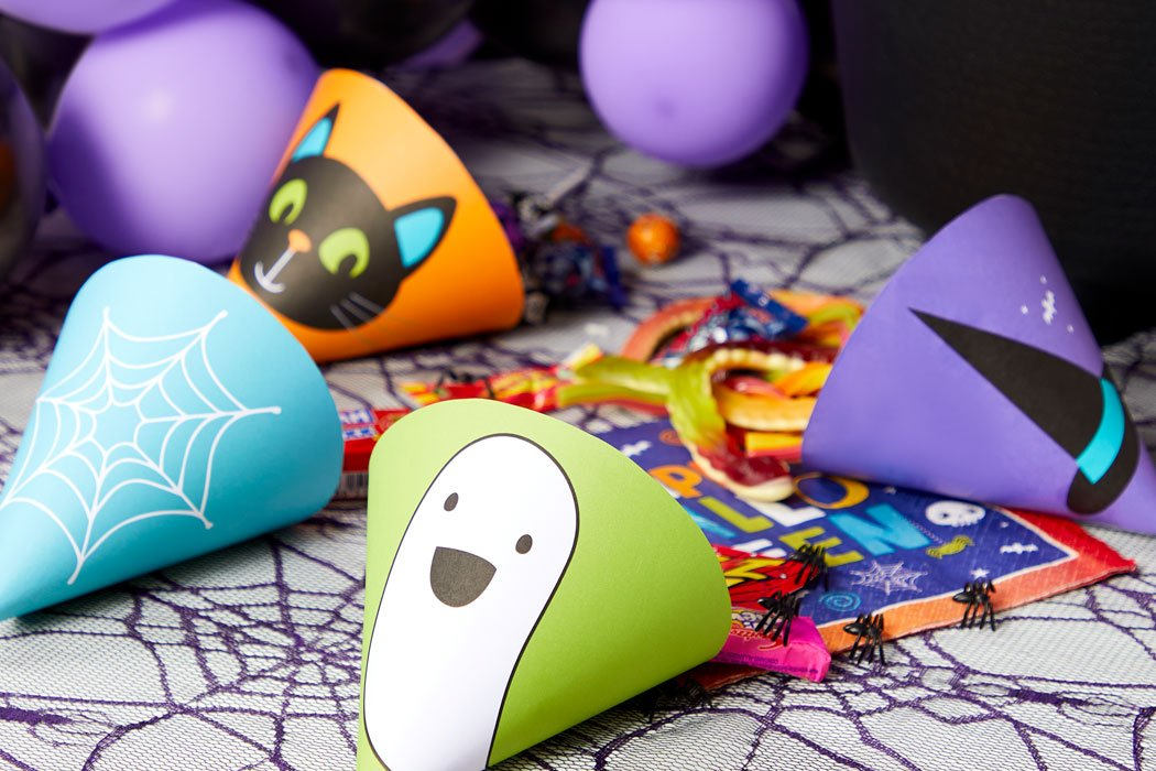Brightly coloured Halloween sweet cones laid out on a table with spiderweb tablecloth and sweets