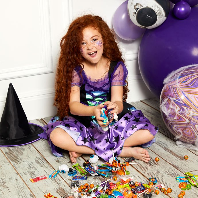 Little girl dressed as a witch hoarding a huge supply of sweets