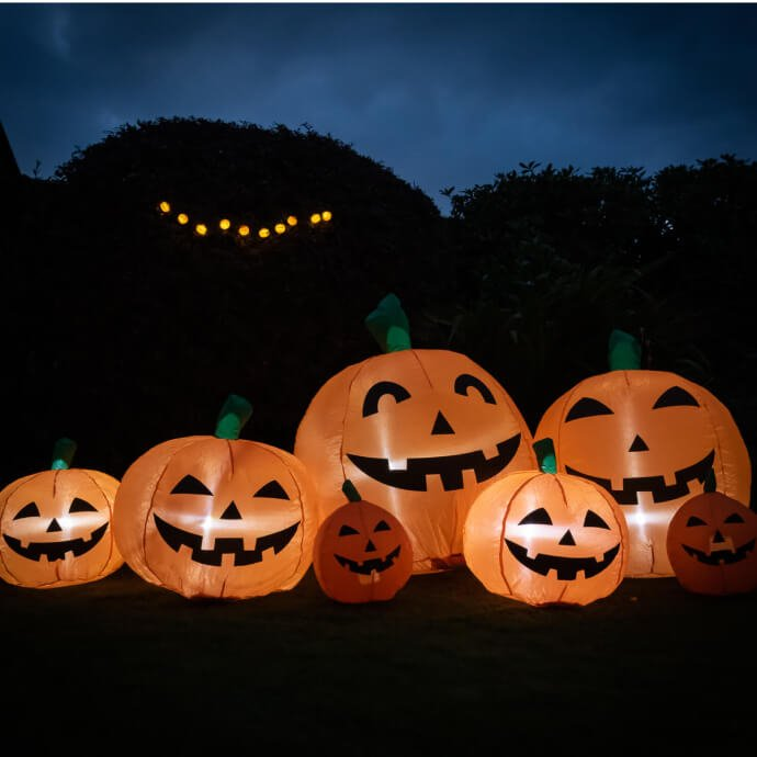 Series of differently sized inflatable pumpkins lit up and on the lawn