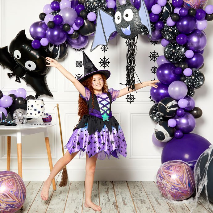 Little girl wearing a witch costume and witch's hat posing in front of a Halloween balloon arch