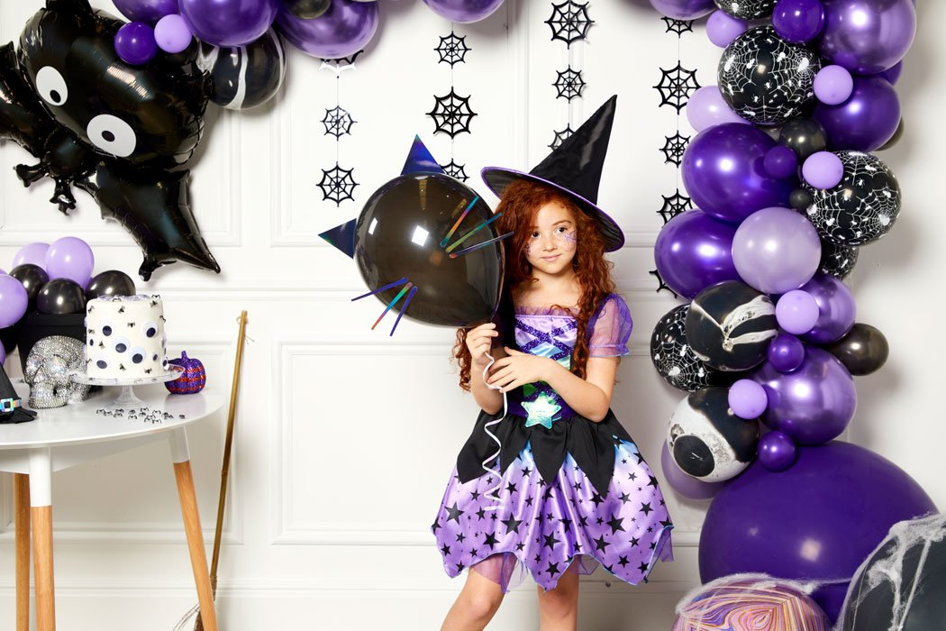 Little girl wearing a witch costume holding a cat balloon in front of a Halloween balloon arch