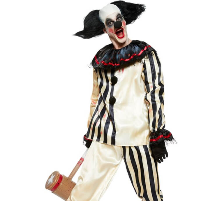 Man in freak show clown costume with black tufted wig and mallet in right hand