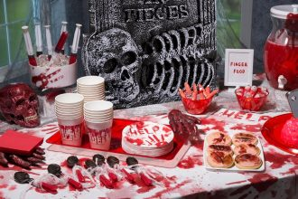 A party table laid out with food, drink and decorations for a Halloween themed party