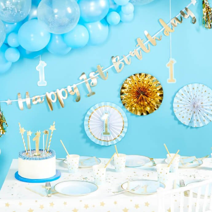 """A table set up with 1st birthday supplies in blue, including a decorated cake, cluster of blue balloons and """"Happy 1st Birthday"""" banner"""