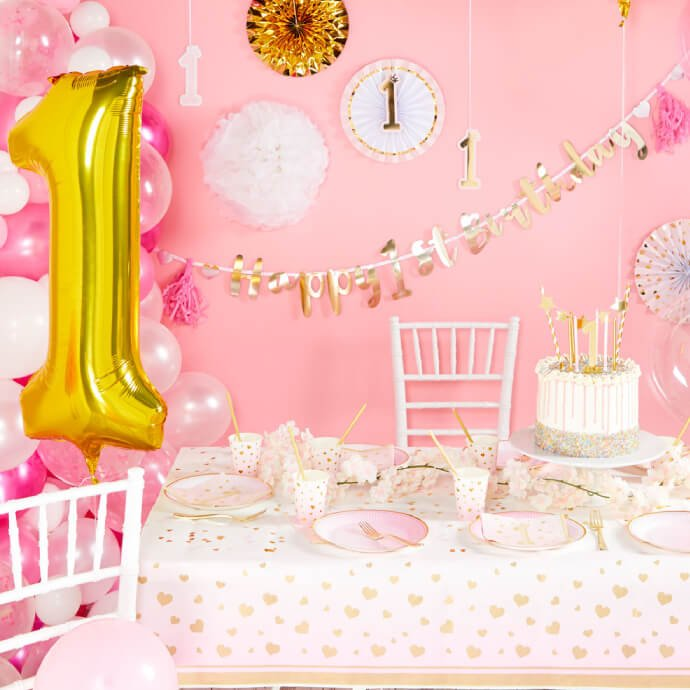 """Table set up with pink 1st birthday tableware with a large golden 1 balloon and """"happy 1st birthday"""" banner"""