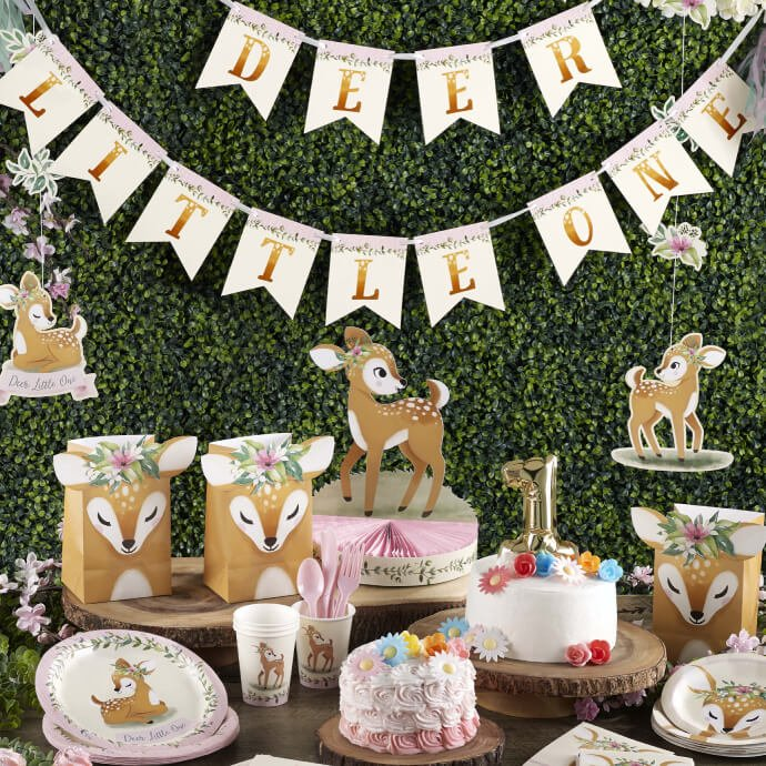 A table set up with Deer Little One party supplies including a banner, large deer centrepiece, deer party bags, plates and cups