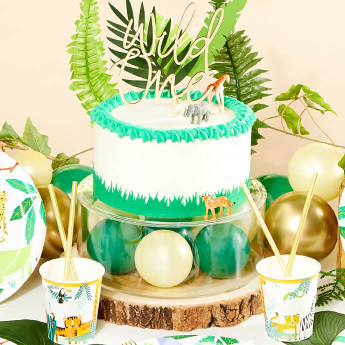 Wild One birthday setup including a white and green cake on cake stand with balloons, leaf decorations, cups and plates