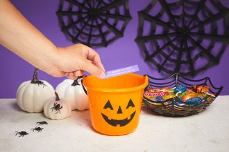 Hand placing a folded up trick or treat into a pumpkin treat bucket