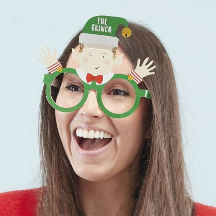 "Woman wearing elf guessing game glasses with elf wearing a hat that says ""The Grinch"""