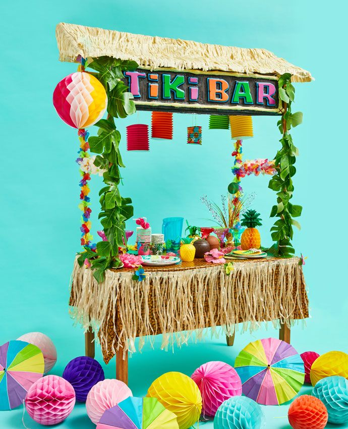Finished Tiki Bar decorated with sign, leaf garlands, hibiscus flower garlands, Hawaiian-themed tableware and summer decorations.