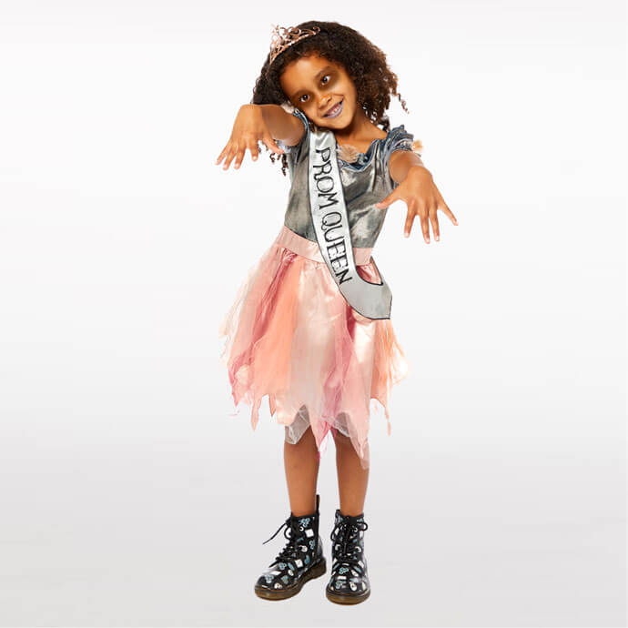 """Young girl wearing a rose gold and silver torn prom dress with """"Prom Queen"""" sash and zombie makeup"""