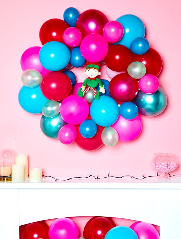 Elf on the Shelf idea - sitting a Christmas wreath made from balloons