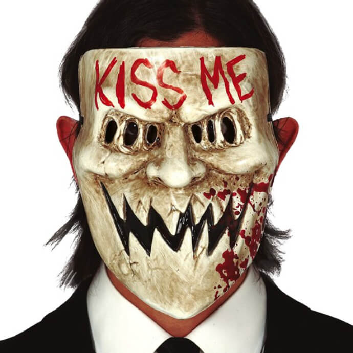Man wearing a mask from The Purge with jagged teeth, hidden eyes and Kiss Me written across the forehead
