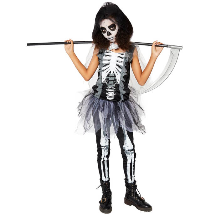 Young girl wearing a skeleton grim reaper outfit with skull print bodysuit, tutu and cape as well as a hood and scythe