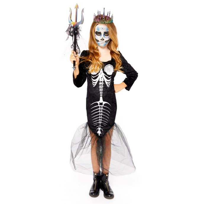 Young girl wearing a long sleeved black velour dress with a mermaid skeleton print and flared net fishtail skirt, holding a trident and wearing a crown