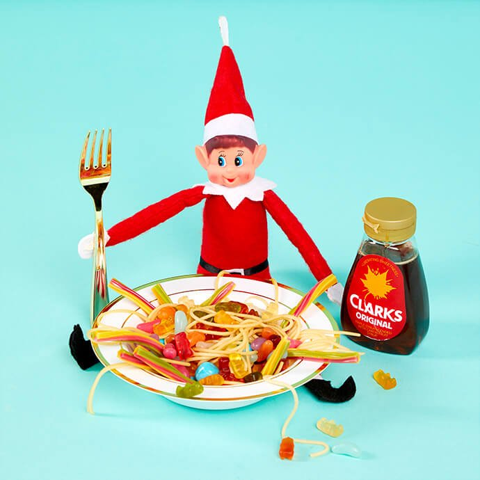 Elf on the Shelf eating a bowl sweets that look like spaghetti