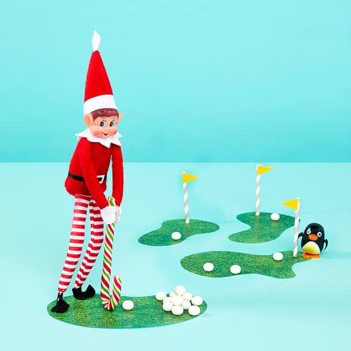 Elf on the Shelf playing golf with a candy cane