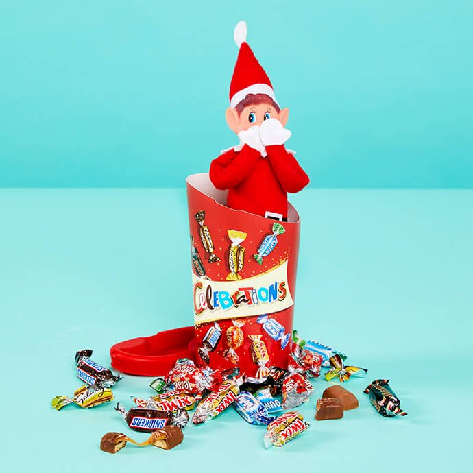 Elf on the Shelf eating a box of Celebrations