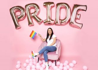 A woman sits on a pink chair surrounded by pink balloons, including PRIDE letter balloons, and waves a rainbow flag