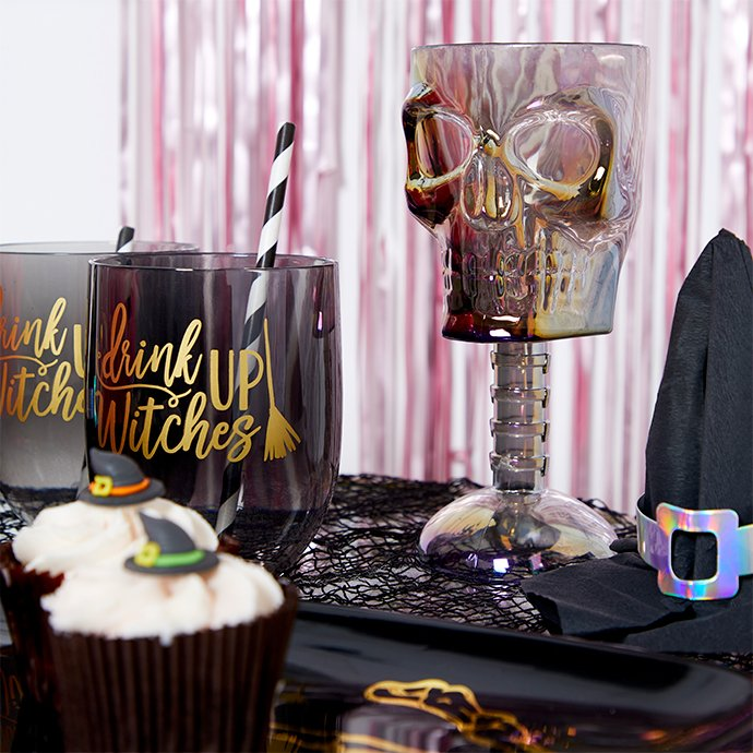 Close up of tableware including cupcakes, witch's hat napkins, skull cups and Drink Up Witches tumblers