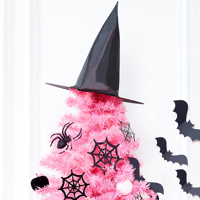 Black witch's hat is perched on top of a pink artificial tree with spiders, cobwebs and bat decorations