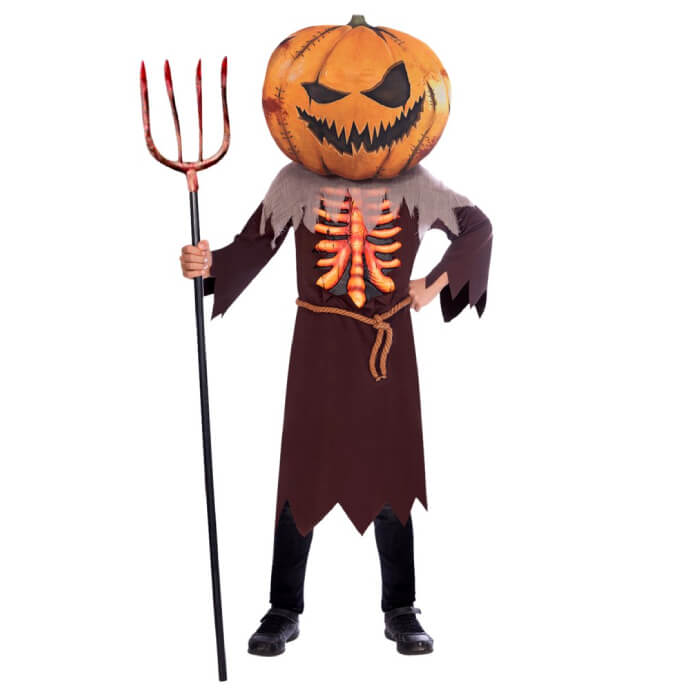 Child wearing an oversized pumpkin head mask, wearing a tunic with ribcage design and holding a pitchfork