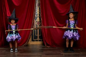 Two young girls wearing withes outfits stand with their broomsticks touching to show a distance of two metres