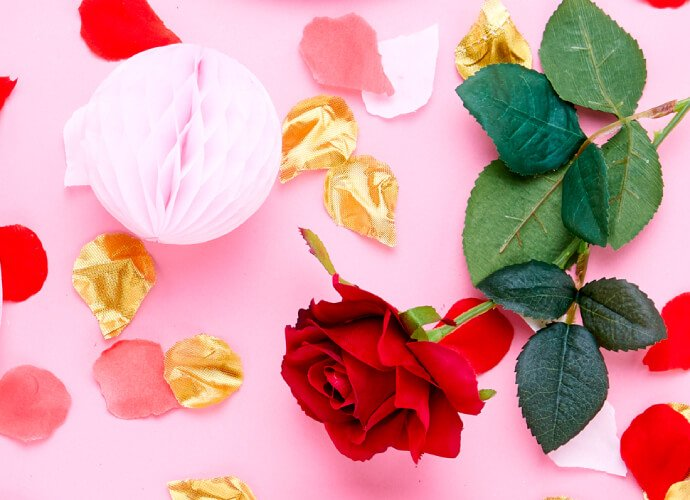 Roses and gold rose petals on a pink background