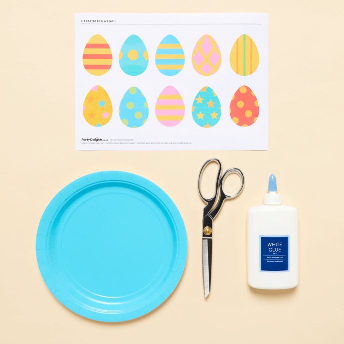 Easter egg printables, paper plate, scissors and glue to make a paper Easter wreath