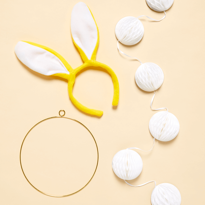 Gold hoop, Easter bunny ears and a string of white pom poms