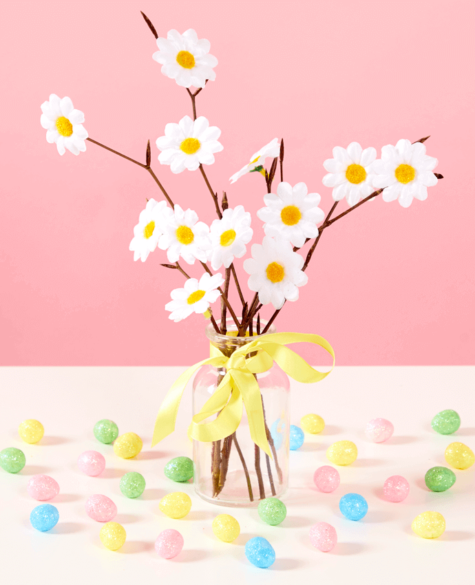 Easter tree made out of natural twigs with daisies stuck on, arranged into a glass bottle and finished off with a ribbon