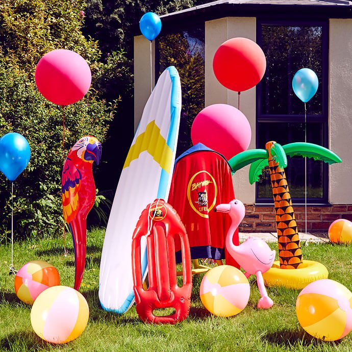 Inflatable surfboard, body board, palm tree, flamingo and parrot in a garden