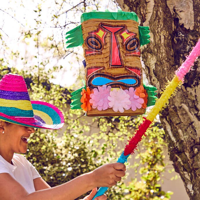A woman with a sombrero covering her eyes attempts to hit a Tiki pinata with a stick