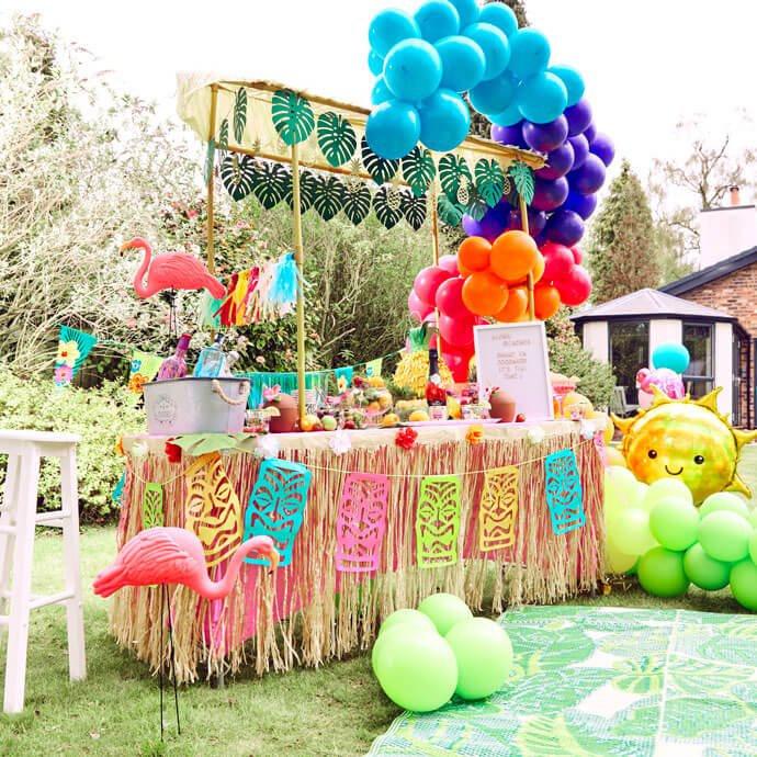 Tiki Bar set up for a beach party with lots of balloons, inflatables and decorations