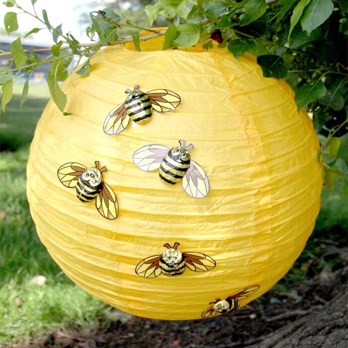 A round yellow paper lantern with chocolate bees stuck over it to look like a beehive