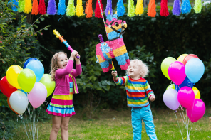Two children in colourful clothes taking hits at a llama pinata with rainbow bunting in the background