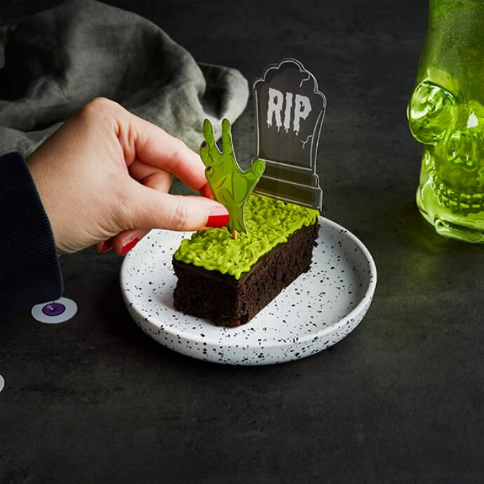 Hand placing a zombie hand cake pick into a chocolate brownie with green frosting