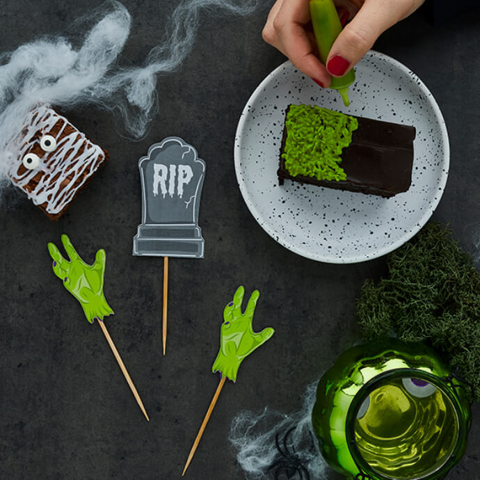 Hand drawing green icing onto a chocolate brownie