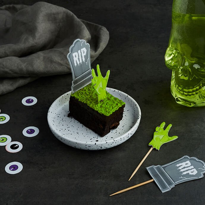 Chocolate brownies topped with green icing, gravestone and zombie hand picks