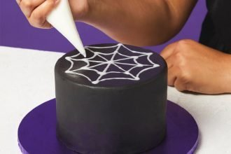 A hand icing a spiderweb onto a black cake for Halloween