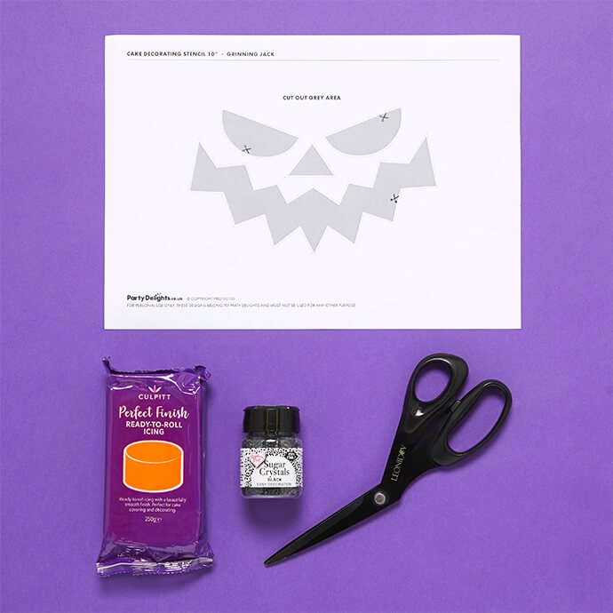 Pumpkin cake stencil printed out with orange icing, black sugar sparkles and a pair of scissors