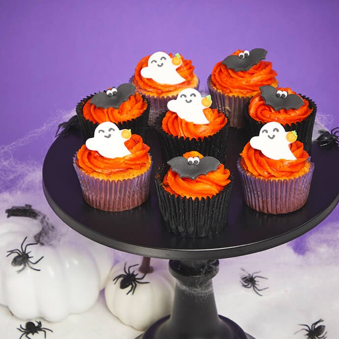 A selection of cupcakes with bright orange swirled icing topped with ghost and bat sugar decorations