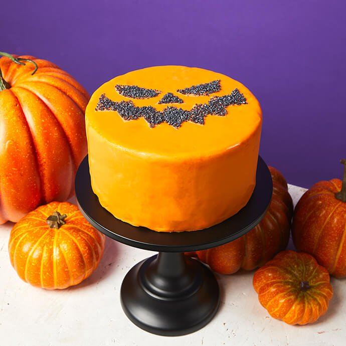 Orange frosted cake with pumpkin stencil sparkling decorations on a table surrounded by mini pumpkins