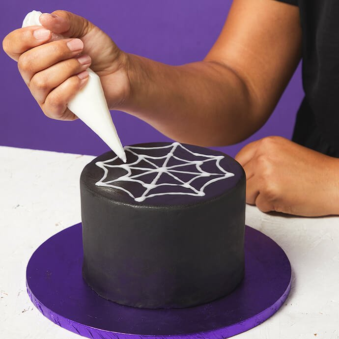 A woman's hands are seen decorating a black cake with a white spiderweb design