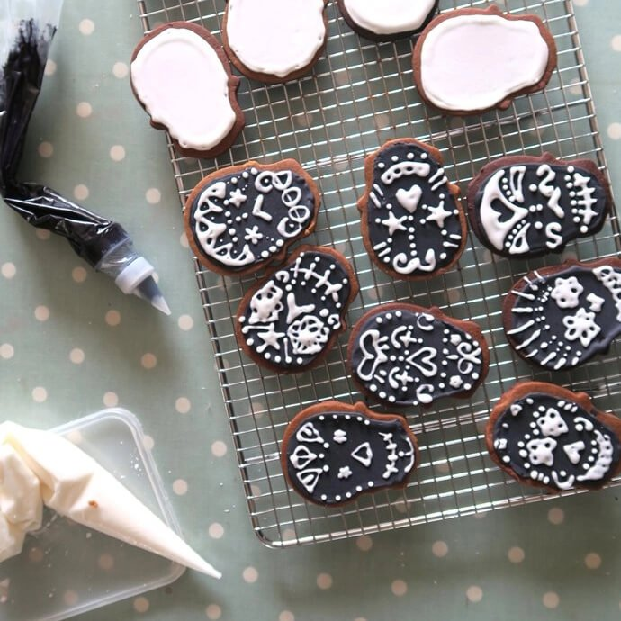 Two sets of skull shaped cookies, one set covered in black icing with white detail and the other with white icing waiting for black detail