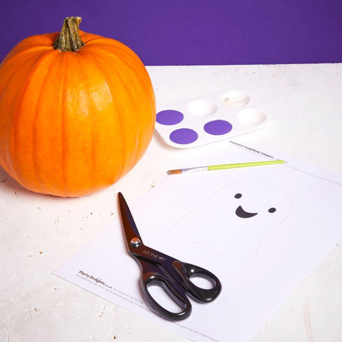 Pumpkin on table with a printed out design, pair of scissors and palette with purple paint in it