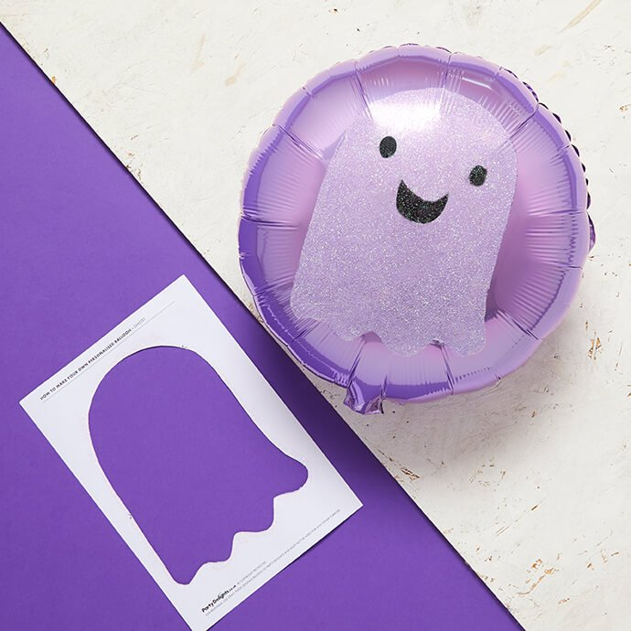 A round purple balloon with glittery ghost design on it