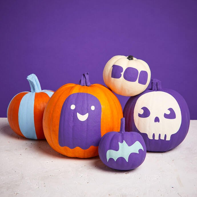 Several pumpkins grouped together and painted with various cute designs